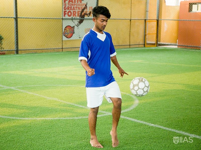 IIAS Male footballer bouncing ball on green field